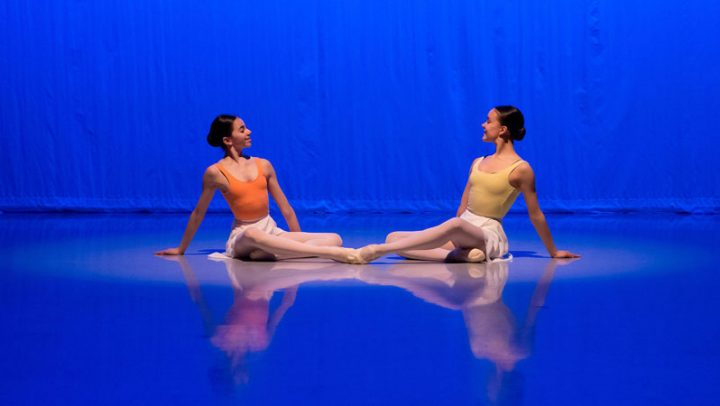 Two students sat on the floor during the 2019 Kenneth MacMillan Emerging Choreographer performance