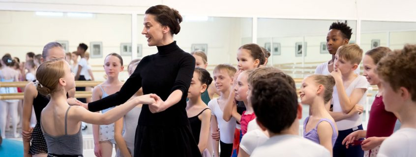 A teacher demonstrating with a student surrounded by a group of young dancers.